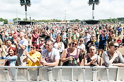 © Licensed to London News Pictures. 13/06/2015. Isle of Wight, UK. Festival goers watch Ward Thomas perform at Isle of Wight Festival 2015 on Saturday Day 3 in the early afternoon sun. Yesterday suffered torrential rain all afternoon and evening, after a first day of warm sun.  This years festival include headline artists the Prodigy, Blur and Fleetwood Mac.  Photo credit : Richard Isaac/LNP