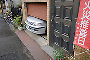 indoor parked car with the nose sticking out as the garage is to small