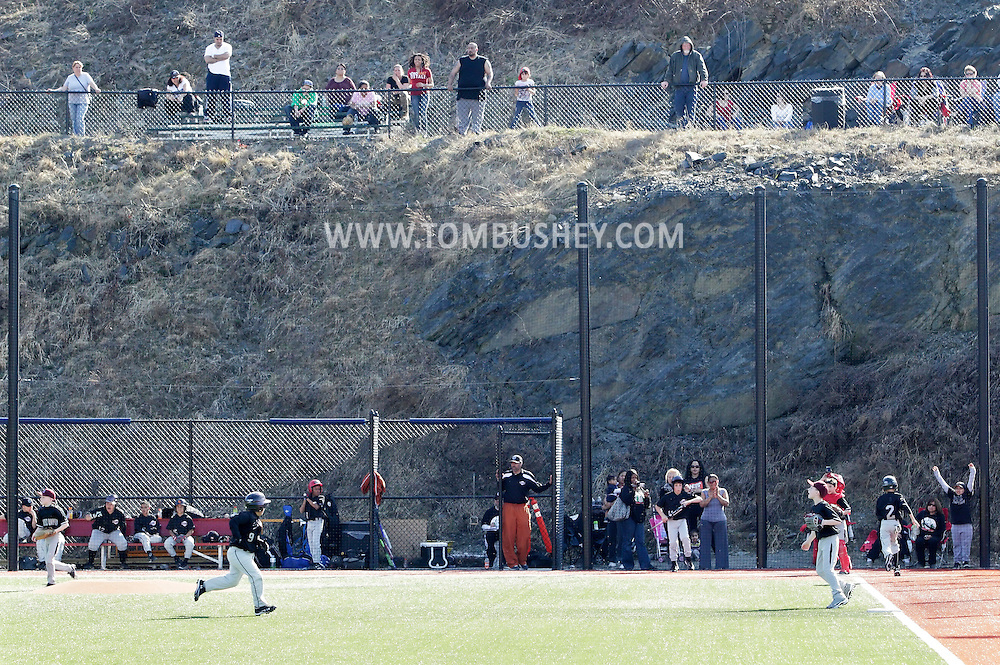 Chester, New York  - A players runs around the bases as fans in the background cheer during the TRUMP March Madness youth baseball tournament at The Rock Sports Park on March 18, 2012. ©Tom Bushey / The Image Works