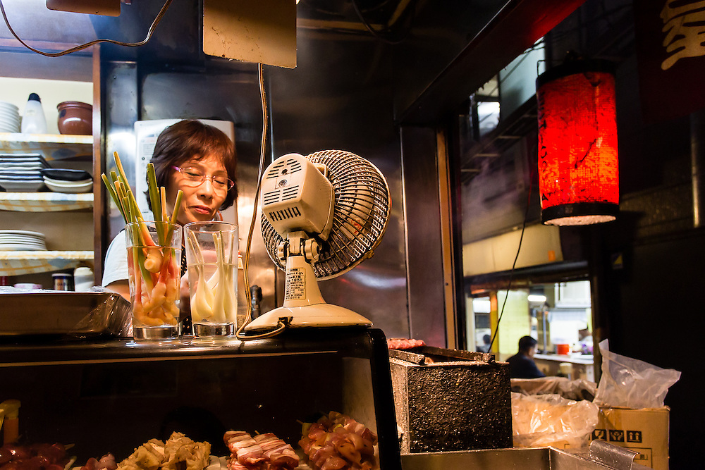 A cook prepares some yakitori (japanese kebabs) in a food stall in a Shinjuku alley