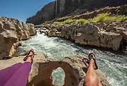 Women relax along a waterfall while exploring along natural springs and rock formations in the Snake River canyon near Twin Falls, Idaho. MR
