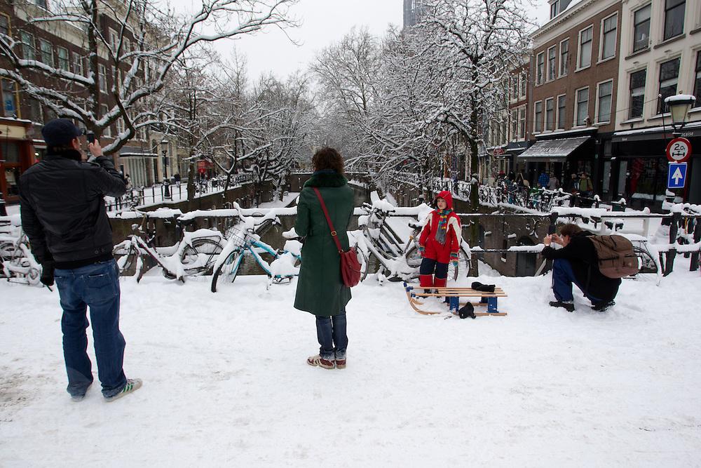 Op een bruggetje over de Oudegracht in Utrecht maken mensen foto's van een besneeuwd landschap. De hevige sneeuwval in Nederland zorgt voor problemen, maar ook voor plezier.<br /> <br /> People are taking pictures of a white center of Utrecht on one of the bridges at the Oudegracht.