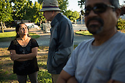 Milpitas residents Latha Narayanan, left, and Graham Bell, center, chat  during National Night Out at Sandalwood Park in Milpitas, California, on August 4, 2016. (Stan Olszewski/SOSKIphoto)