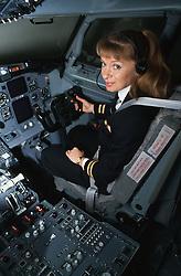 Female pilot sitting at aeroplane controls,