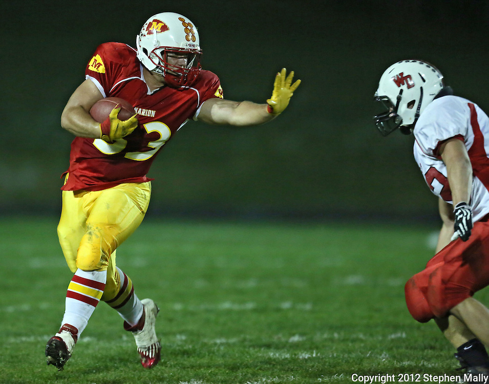 Marion's Trev Biery (33) tries to stiff arm Western Dubuque's Blake Kass (42) on a run during their first round playoff game at Thomas Park Field in Marion on Wednesday, October 24, 2012.