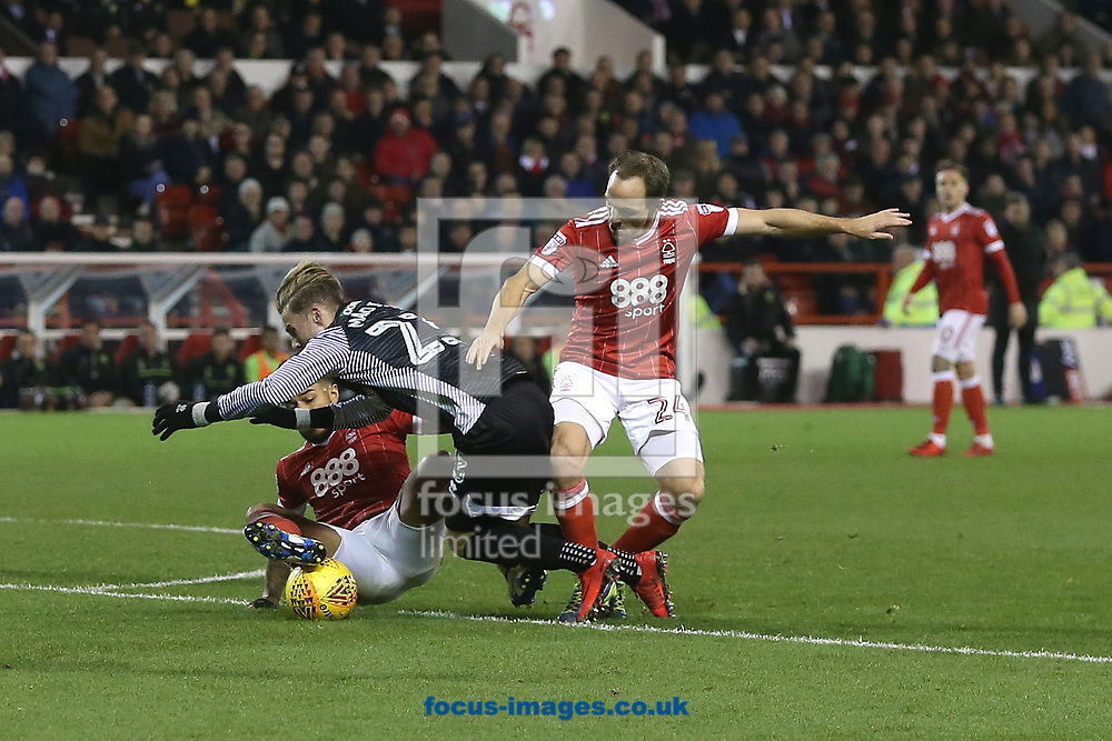 James Maddison of Norwich goes down under pressure from Liam Bridcutt of Nottingham Forest and David Vaughan of Nottingham Forest  but no foul is awarded by Referee Tony Harrington during the Sky Bet Championship match at the City Ground, Nottingham<br /> Picture by Paul Chesterton/Focus Images Ltd +44 7904 640267<br /> 21/11/2017