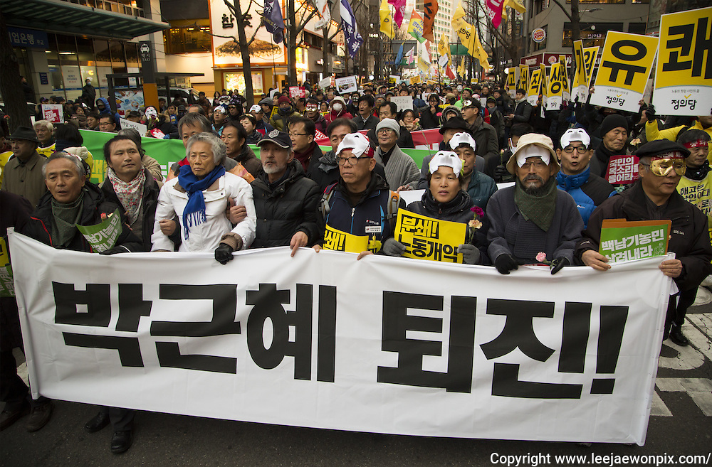 "Progressive activist Baek Gi-wan (3rd L, front) and other activists march during an anti-government rally in Seoul, South Korea, December 5, 2015. The ""People's Camp for Rising Up and Fighting"", representing various groups of farmers, students, workers and the poor, demonstrated to oppose South Korean President Park Geun-hye to change the labor market which protesters insist, will allow easier layoff and more temporary workers and to monopolize the authorship of history textbooks. People wore masks at the rally to denounce Park who recently compared local protestors in masks to ISIS. The organizer said 50,000 people participated in the demo, while the police estimated that 14,000 attended. Placard reads,""Park Geun-hye resign!"". Photo by Lee Jae-Won (SOUTH KOREA)  www.leejaewonpix.com"