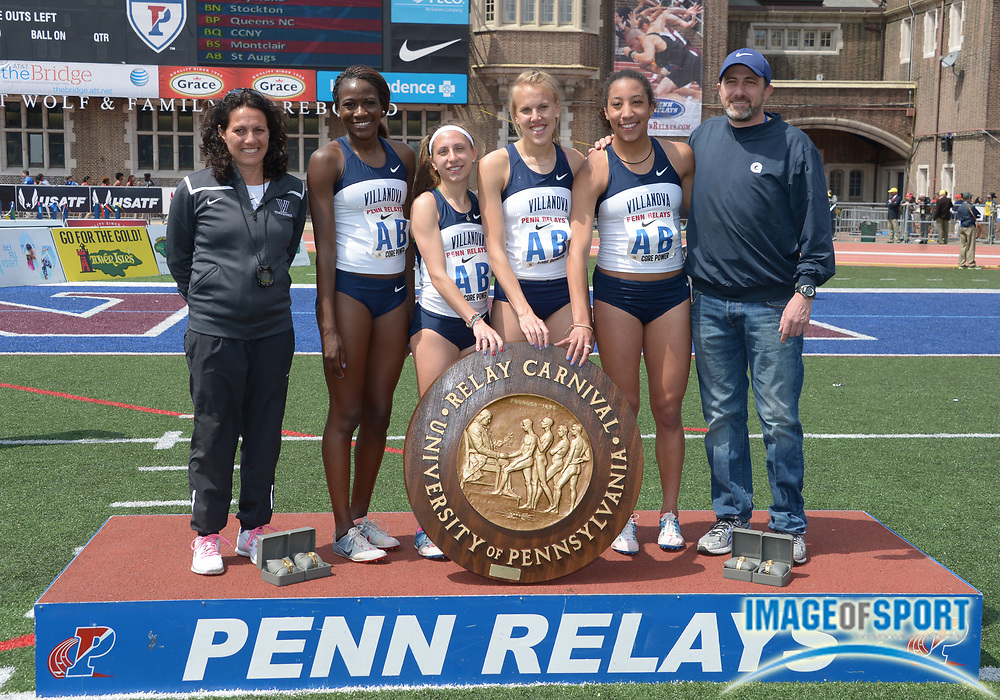 Apr 25, 2014; Philadelphia, PA, USA; Members of the Villanova womens 4 x 1,500m relay pose with the pinwheel after winning the Championship of America race in 17:16.52 in the 120th Penn Relays at Franklin Field. From left: Villanova coach Gina Procaccio  and Nicky Akande and Emily Lipari and Stephanie Schappert and Angel Piccirillo and Mike Stahr.