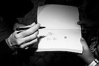 """NAPOLI, 23 APRILE 2016:  Silver, pseudonimo di Guido Silvestri, autore del personaggio """"Lupo Alberto"""", firma e disegna una dedica per un fan alla XVIII edizione di Comicon, il salone internazionale del fumetto a Napoli, il 23 aprile 2016.<br /> <br /> ###<br /> <br /> NAPLES, ITALY - 23 APRIL 2016: Silver, pseudonym of Guido Silvestri, author of the series """"Lupo Alberto"""", signs and draws an inscription for a fan at the XVIII edition of Comicon, the international comics fair in Naples, Italy, on April 23rd 2016."""