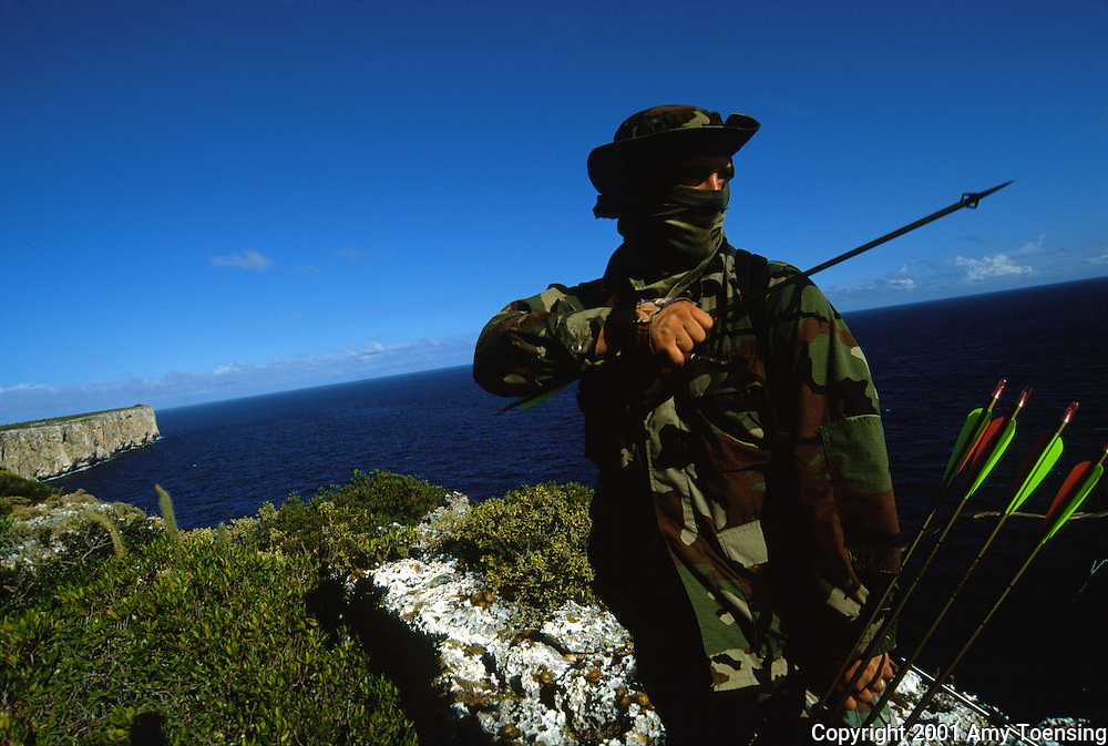 MONA ISLAND, PR - DECEMBER 05: A hunter makes his way along the cliffs of Mona Island on the lookout for feral prey December 5, 2001, on Mona Island, Puerto Rico. From December through April, hunting is permitted in order to control the population of non-endemic species such as pigs and goats. Puerto Rico was an outpost of Spanish colonialism for 400 years, until the United States took possession in 1898. Today Puerto Rico's Spanish-speaking culture reflects its history - a mix of African slaves, Spanish settlers, and Taino Indians. Puerto Ricans fight in the U.S. armed forces but are not entitled to vote in presidential elections. They passionately debate their relationship with the U.S. with about half the island wanting to become the 51st state and the other half wanting to remain a U.S. commonwealth. A small percentage feel the island should be an independent country. While locals grapple with the evils of a burgeoning drug trade and unchecked development, drumbeats still drive the rhythms of African-inspired bomba music. (Photo By Amy Toensing) _________________________________<br />