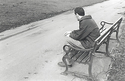 Young man sitting alone on park bench,