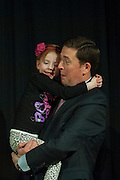 Vice President of Student Affairs Ryan Lombardi holds his daughter while the contestants wait for the winner to be announced during the 2015 Ava Nichols Faculty Pageant in Baker University Ballroom on Wednesday, February 25.