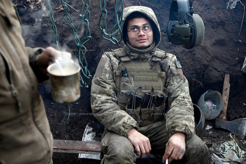 Charlie takes a short break in the trench and looks up to Alex who&acute;s drinking a cup of tea.<br />