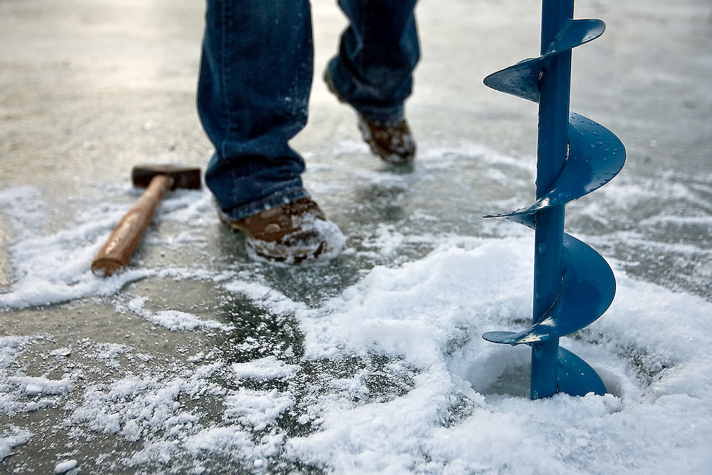 JEROME A. POLLOS/Press..An auger and a hammer are the first step for ice fishing and can take some effort as the ice grows thicker.