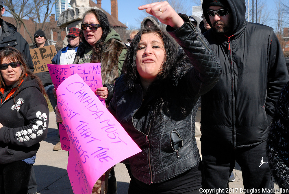 CANADA, Windsor. 04 March 2017. A Canadian Coalition of Concerned Citizens demonstration at City Hall at noon is met by a counter demonstration group. There is some minor pushing, heated debate and occasional threats. The demonstration is spurred in part by M-103, a federal anti-Islamophobia motion. NOTE: Agefotostock exclusive image, G99-2864924, to license go to http://www.agefotostock.com/age/en/Stock-Images/Rights-Managed/G99-2864924