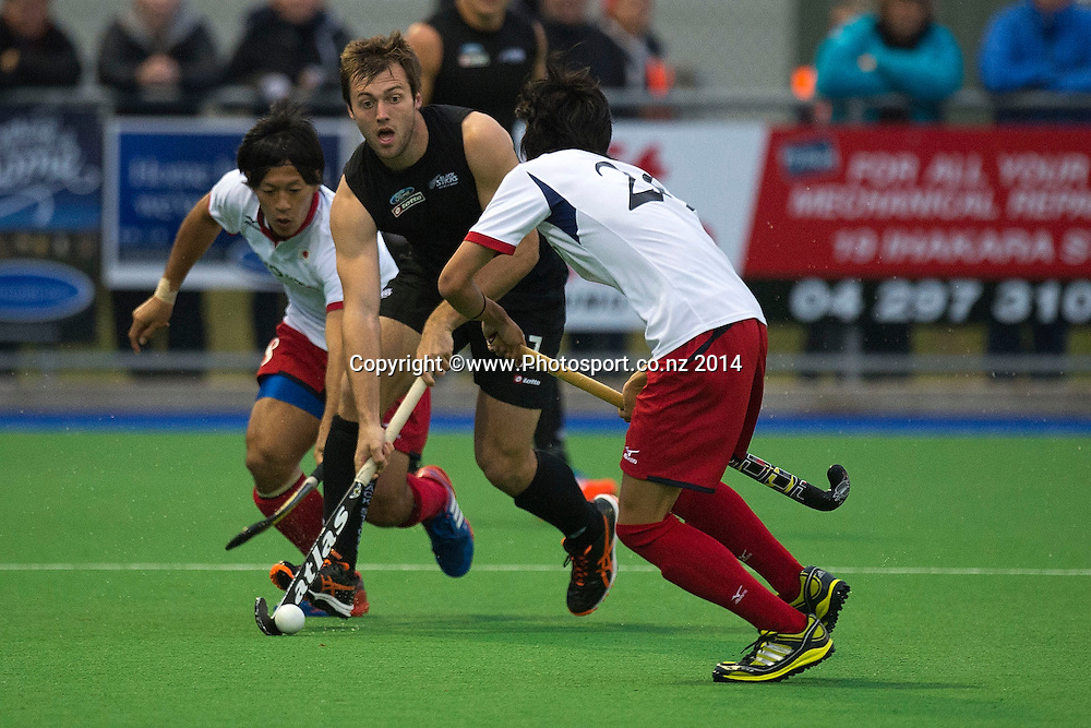 Nic Woods (C of New Zealand is tackled by Koshi Yamabe and Kazuma Murata of Japan during the Black Sticks Men v Japan international hockey match at the Coastlands Kapiti Sports Turf in Paraparaumu on Friday the 21st of November 2014. Photo by Marty Melville/www.Photosport.co.nz