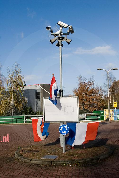cameratoezicht op de rotonde bij een afvalbrengpunt in enschede ( vlierstraat ) versiersd met nederlandse vlaggen.