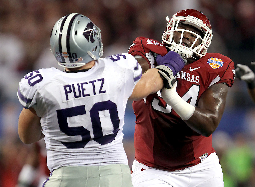Kansas State offensive lineman Nick Puetz (50) fights off a Arkansas defensive lineman during the first half of the Cotton Bowl Friday, Jan. 6, 2012, in Arlington, Texas.