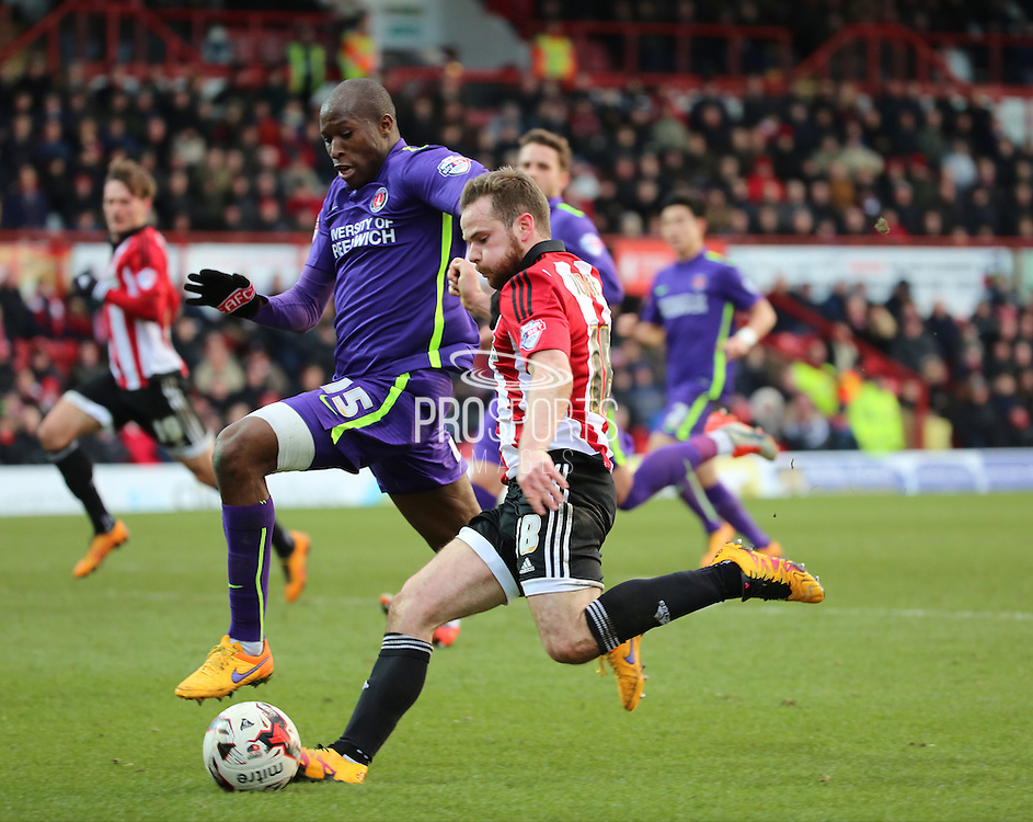 Brentford midfielder, Alan Judge (18) trying to take on Charlton Athletic defender, Rod Fanni (15) during the Sky Bet Championship match between Brentford and Charlton Athletic at Griffin Park, London, England on 5 March 2016. Photo by Matthew Redman.