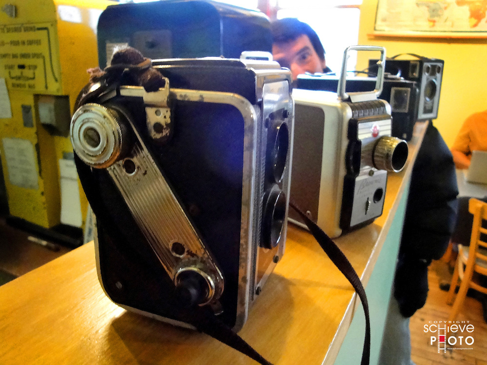 Antique cameras in a coffee shop and some guy in the back ground.