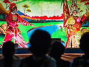 17 FEBRUARY 2016 - BANGKOK, THAILAND:  People watch a Chinese opera performance at a small shrine in Bangkok. The small troupe travels from Chinese shrine to Chinese shrine performing for a few nights before going to another shrine. They spend about half the year touring in Thailand and the other half of the year touring in Malaysia. Members of the troupe are paid about 5,000 Thai Baht per month (about $140 US). Chinese opera was once very popular in Thailand, where it is called Ngiew. It is usually performed in the Teochew language. Millions of Chinese emigrated to Thailand (then Siam) in the 18th and 19th centuries and brought their culture with them. Recently the popularity of ngiew has faded as people turn to performances of opera on DVD or movies. There are still as many 30 Chinese opera troupes left in Bangkok and its environs. They are especially busy during Chinese New Year and Chinese holiday when they travel from Chinese temple to Chinese temple performing on stages they put up in streets near the temple, sometimes sleeping on hammocks they sling under their stage. Most of the Chinese operas from Bangkok travel to Malaysia for Ghost Month, leaving just a few to perform in Bangkok.    PHOTO BY JACK KURTZ