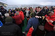 Ship officer baptises first-time Arctic Circle passengers aboard Hurtigruten coastal cruise ship sailing along northwest coast of Norway.