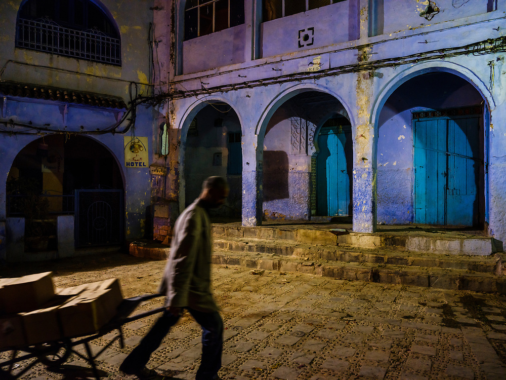 CHEFCHAOUEN, MOROCCO - CIRCA APRIL 2017: Man walking by a square in Chefchaouen at night. This is a popular tourist destination in Morocco.