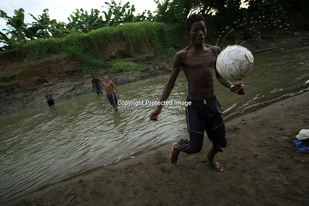 Kids play soccer in a river that runs by a banana plantation just outside of Apartado, on July 9, 2007. (Photo/Scott Dalton)