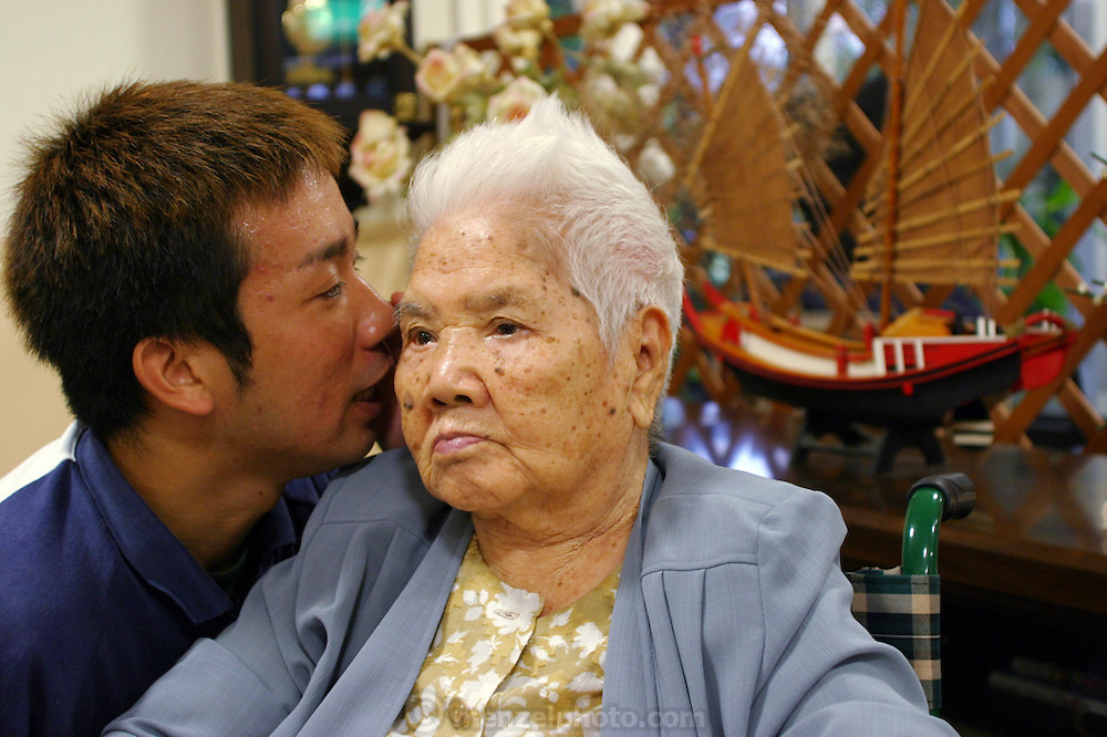 "Mie Ohshiro, 100 years old and slightly deaf, listens intently as 28-year-old nursing home aid Satoru Yamanoha repeats a question posted by a visitor about this Naga City Okinawa day care facility. ""I enjoy it because I have lots of friends here,"" she says, ""and my son and his wife also use this place."" Mie lives with her second son and his family but comes to the center two or three times a week for a traditional Okinawan lunch, physical therapy, and companionship."