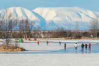 Mount Susitna rises behind skaters and walkers on the ice track at Westchester Lagoon in Anchorage, Alaska.