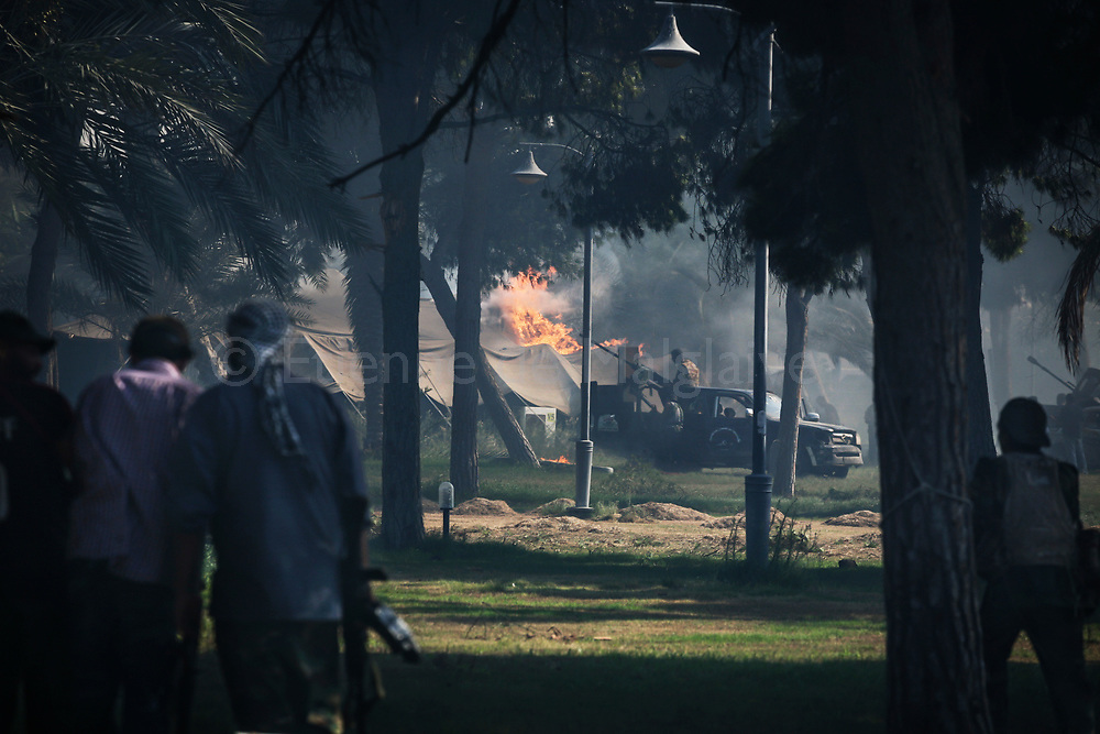 Libyan rebels  attack Bab Al Azizyia,  Gadhafi's headquarters compound in Tripoli. After a Caterpillar open a breach in the outer wall and rammed the main gate, the rebels swarm the compound setting the bedouin tents on fire while dodging adverse fire shots.<br /> 23 August 2011.