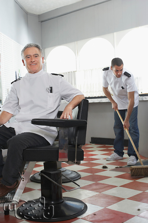 Two barbers in barber shop one sweeping floor