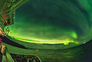 The sweep of the auroral oval from a latitude of 70&deg; north in the Barent&rsquo;s Sea off the north coast of Norway, on October 26, 2017. The curtains exhibit a lower pink fringe from nitrogen. <br /> <br /> Taken from the forward deck of the m/s Nordlys<br /> <br /> This is a single 2-second exposure with the 12mm Rokinon full-frame fish-eye lens at f/2.8 and Nikon D750 at ISO 6400.