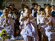31 DECEMBER 2017 - BANGKOK, THAILAND: Buddhist nuns participate in an overnight prayer and chanting service on New Year's Eve at Wat Pathum Wanaram in central Bangkok. The strings attached to their heads unite and amplify the prayers. Many Thais go to temples and shrines to pray and meditate during New Year's Eve and New Year's Day.    PHOTO BY JACK KURTZ