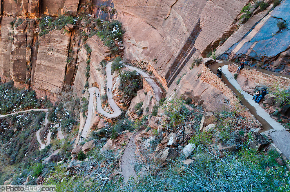 Hikers ascend impressive switchbacks of the West Rim Trail on the way to Angels Landing and Scout Lookout. Zion National Park adjoins Springdale, Utah, USA. The North Fork of the Virgin River carved spectacular Zion Canyon through reddish and tan-colored Navajo Sandstone up to half a mile (800 m) deep and 15 miles (24 km) long. Uplift associated with the creation of the Colorado Plateaus lifted the region 10,000 feet (3000 m) starting 13 million years ago. Zion and Kolob canyon geology includes 9 formations covering 150 million years of mostly Mesozoic-aged sedimentation, from warm, shallow seas, streams, lakes, vast deserts, and dry near-shore environments. Mormons discovered the canyon in 1858 and settled in the early 1860s. U.S. President Taft declared it Mukuntuweap National Monument in 1909. In 1918, the name changed to Zion (an ancient Hebrew name for Jerusalem), which became a National Park in 1919. The Kolob section (a 1937 National Monument) was added to Zion National Park in 1956. Unusually diverse plants and animals congregate here where the Colorado Plateau, Great Basin, and Mojave Desert meet.
