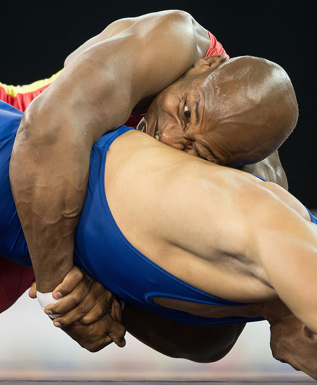 Cristian Mosquera (top) of Colombia  grimaces as he struggles with Querys Perez of Venezuela during their semi-final bout in the 85kg class of the men's greco-roman wrestling  at the 2015 Pan American Games in Toronto, Canada, July 15,  2015.  AFP PHOTO/GEOFF ROBINS