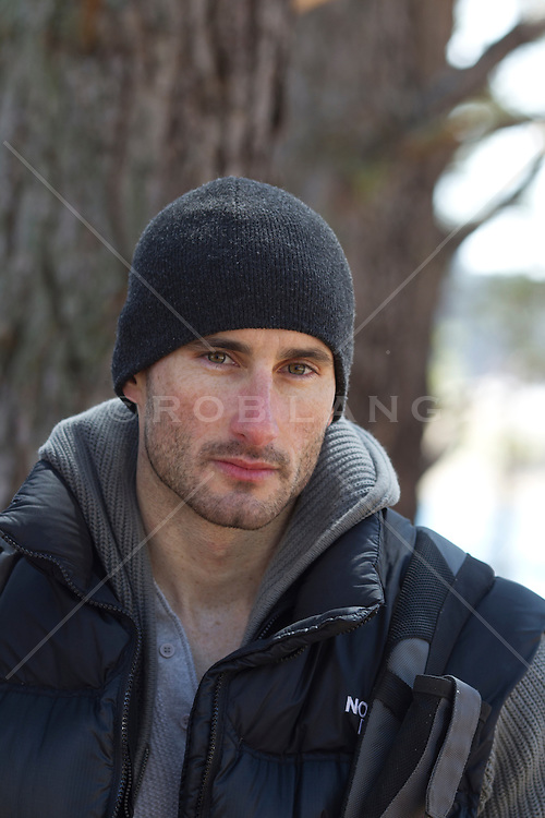 handsome rugged man outdoors by a tree