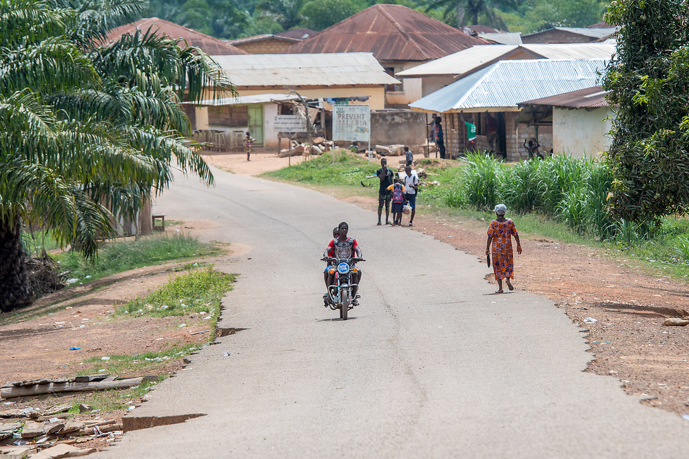 People walking and a man riding a motorcycle on Monrovia road in Ganta, Liberia