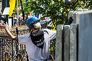 01 DECEMBER 2013 - BANGKOK, THAILAND: A Thai man throws a rock towards the police lines during the anti-government riot. Thousands of anti-government Thais confronted riot police at Phanitchayakan Intersection, where Rama V and Phitsanoluk Roads intersect, next to Government House (the office of the Prime Minister). Protestors threw rocks, cherry bombs, small explosives and Molotov cocktails at police who responded with waves of tear gas and chemical dispersal weapons. At least four people were killed at a university in suburban Bangkok when gangs of pro-government and anti-government demonstrators clashed. This is the most serious political violence in Thailand since 2010.    PHOTO BY JACK KURTZ