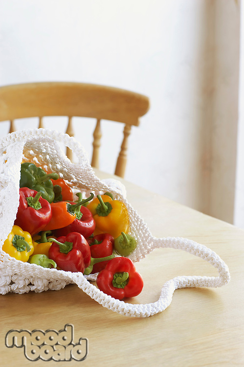 Bag full of bell peppers on table close-up