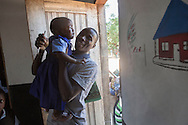 Volunteer teacher, Bright Kachepa, comforts a student at the Alinafe Community Based Childcare Center in Mjambe Village near Zomba, Malawi. The volunteer teachers who run the centers have received training from a local CRS project through a Conrad N. Hilton Foundation grant. The project known as THRIVE focuses on early childhood development and includes special support for childcare centers, children's health and nutrition and lessons in positive parenting. The Alinafe center started under a tree and is now a full fledged building.
