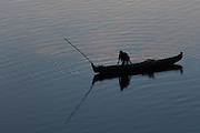 Man standing in fishing boat making ripples in water