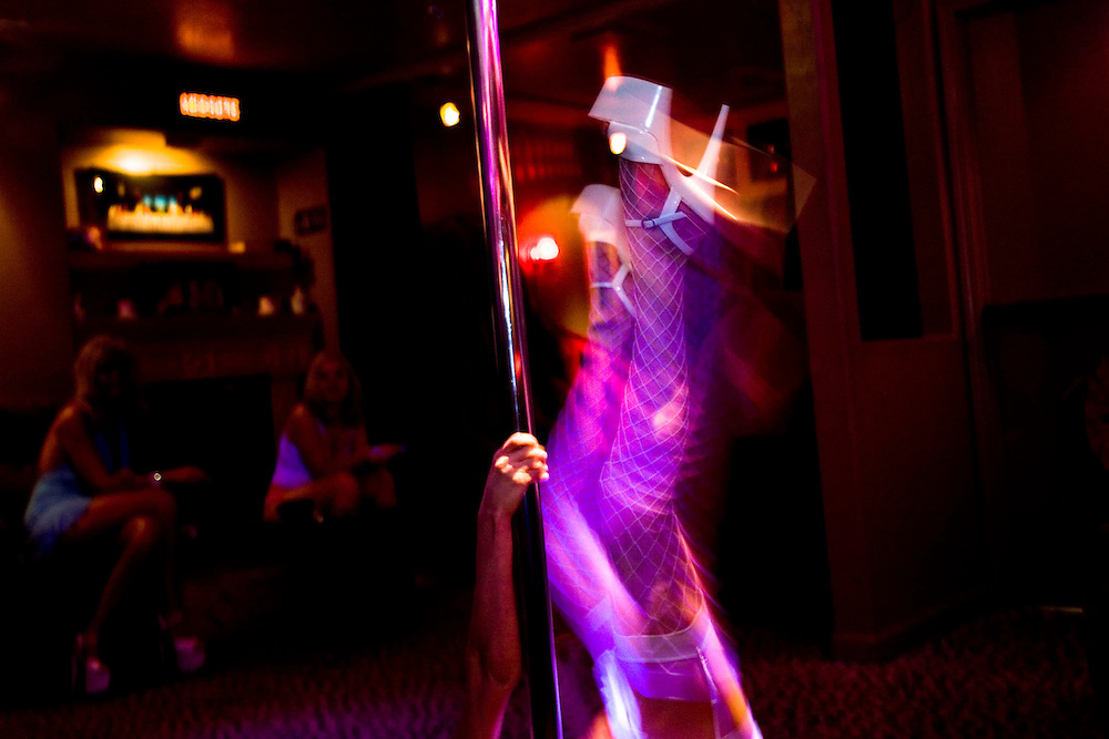 "Sex worker Mila Moore works the pole in the parlor of the Moonlite Bunny Ranch brothel in Mound House, NV on Saturday, July 28, 2006...The Moonlite Bunny Ranch brothel in Mound House, Nevada - just a few miles from the state capital in Carson City - first opened in 1955. The Ranch is a legal, licensed brothel owned by Dennis Hof. It's featured in the HBO series ""Cathouse."""