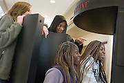 Liz Westendorf (from left), Jason Fox, Tahirah Nyanin and Jasmine Merith check out The Human Race Machine installment at O.U.'s new Baker Center on Tuesday, 1/08/07. The machine morphs the participants' faces to show what they might look like if they belonged to another race.