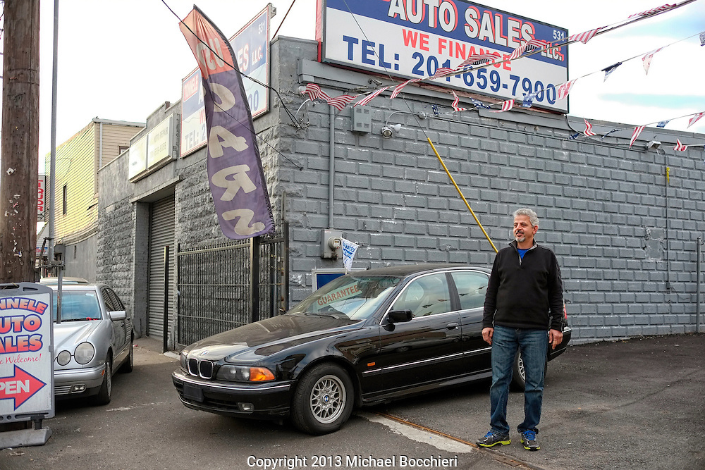JERSEY CITY, NJ - December 27:  Ashraf Amer stands in front of his used auto lot, Tonnele Auto Sales, LLC on U.S. Route 1/9 December 27, 2013 in JERSEY CITY, NJ. Formed in 1926 it connects junction in Woodbridge Township, Middlesex County, New Jersey north to New York City.  (Photo by Michael Bocchieri/Bocchieri Archive)