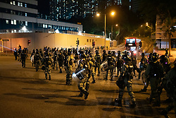 Hong Kong, China. 9th October 2019. Large peaceful crowd gathered to sing songs at MOStown mall in Ma On Shan in solidarity with several security guards who were arrested by police this week. Later small group of protestors went to nearby Shatin Divisional Police Station and shouted abuse at the police and threw objects. Riot police later charged but no arrests made. Police return to police station  after failing to make arrests after charge.  Iain Masterton/Alamy Live News.