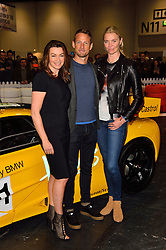 © Licensed to London News Pictures. 18/02/2016. SUZI PERRY, JENSEN BUTTON and JODIE KIDD poses with a MACLAREN F1 car at the launch of the London Classic Car Show.  The four day event brings together classic car owner, dealers, collectors, experts and enthusiasts. London, UK. Photo credit: Ray Tang/LNP