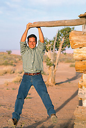 Man playing around on a piece of wood jutting out from a wooden cabin