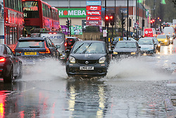 © Licensed to London News Pictures. 20/12/12/019. London, UK. Buses and cars travel through a flood on Green Lanes, Harringay in North London, caused by overnight heavy rainfall and a pipe burst.  Photo credit: Dinendra Haria/LNP