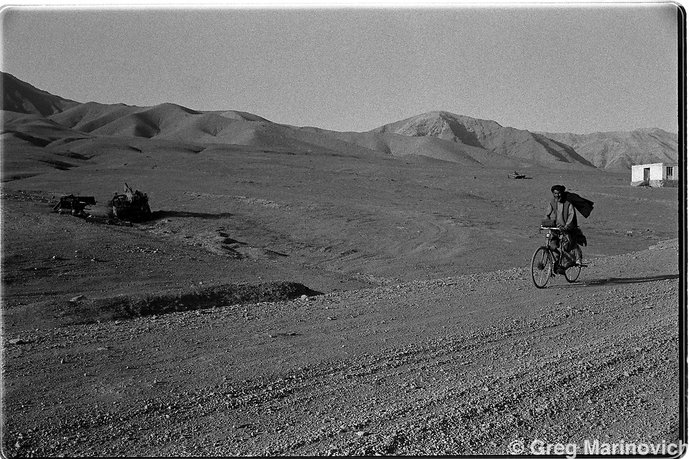 An Afghan cycles along a road marked only by tank debris. (Greg Marinovich)